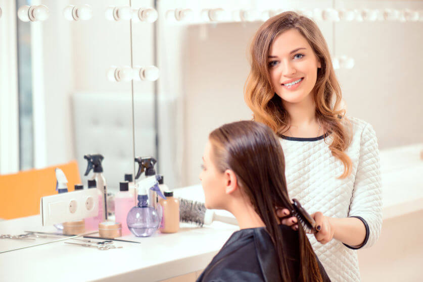 Hairdresser with client in salon smiling
