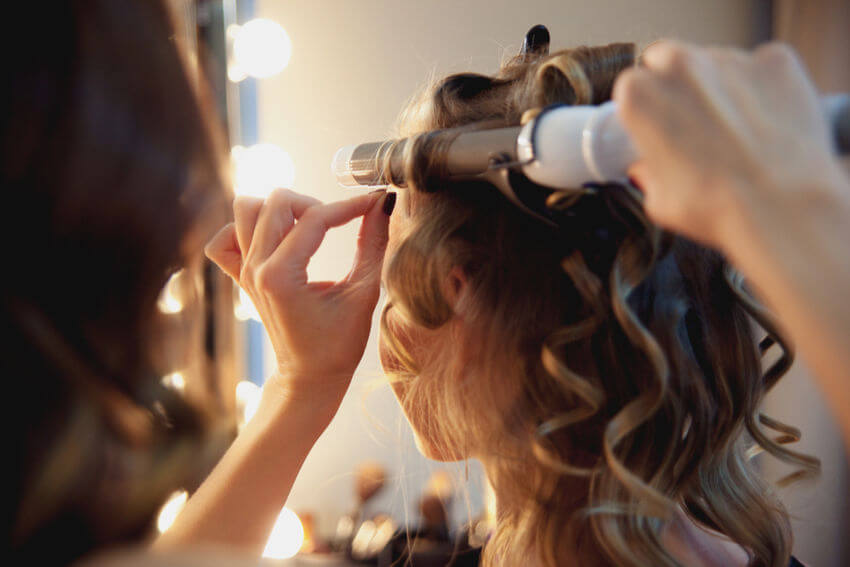 hairdresser curling hair with electric curling tong for party season