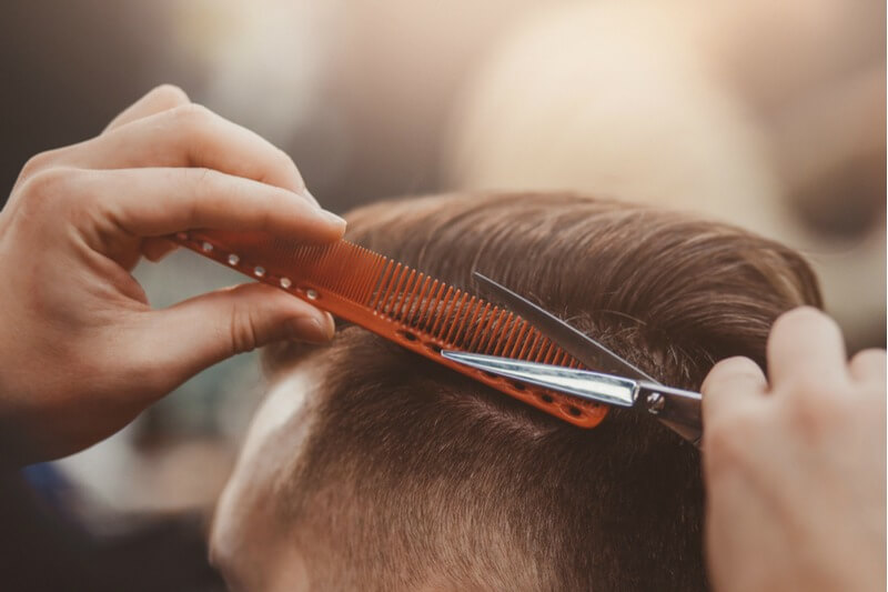 Barber scissors cutting hair over comb